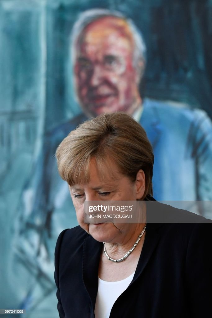German Chancellor Angela Merkel walks past the official portrait of former German Chancellor Helmut Kohl after she signed his book of condolence at the Chancellery in Berlin on June 18, 2017. Helmut Kohl, the former German chancellor who seized the chance to reunite his country after years of Cold War separation, died at the age of 87 on June 16, 2017. / AFP PHOTO / John MACDOUGALL