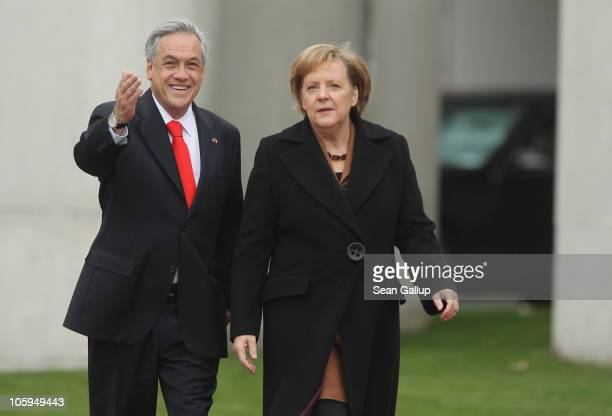 German Chancellor Angela Merkel walks with Chilean President Sebastian Pinera to review a guard of honour upon his arrival at the Chancellery on...