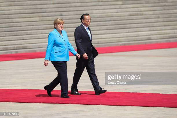 German Chancellor Angela Merkel walks with China's Premier Li Keqiang during a welcome ceremony outside the Great Hall of the People on May 24 2018...