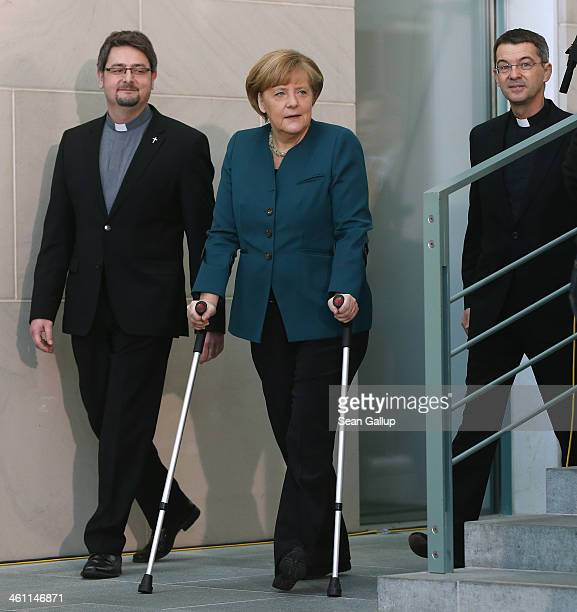 German Chancellor Angela Merkel walks with crutches as she arrives for a gathering of child Epiphany singers dressed as the Three Kings at the...