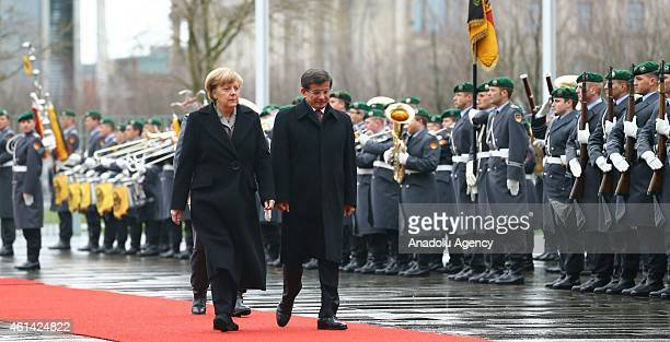 German Chancellor Angela Merkel walks with Turkish Prime Minister Ahmet Davutoglu within the official honor guards' welcoming ceremony during...