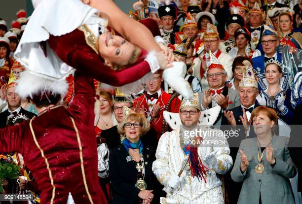 German Chancellor Angela Merkel watches a performance of carnival dancers Selina and Alexei Balzer as she receives royal couples of the federal...