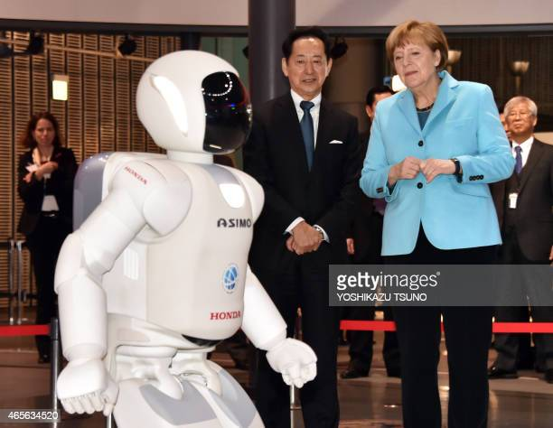 German Chancellor Angela Merkel watches a running performance by Japanese auto giant Honda Motor's humanoid robot Asimo as museum head and former...