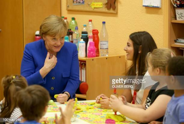 German Chancellor Angela Merkel receives a selfdesigned book made by the children of the kindergarten as she visits a Caritas center in Cologne...