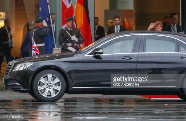 German Chancellor Angela Merkel waves as British Prime Minister Theresa May leaves in her car at the Chancellery in Berlin on December 11 prior...