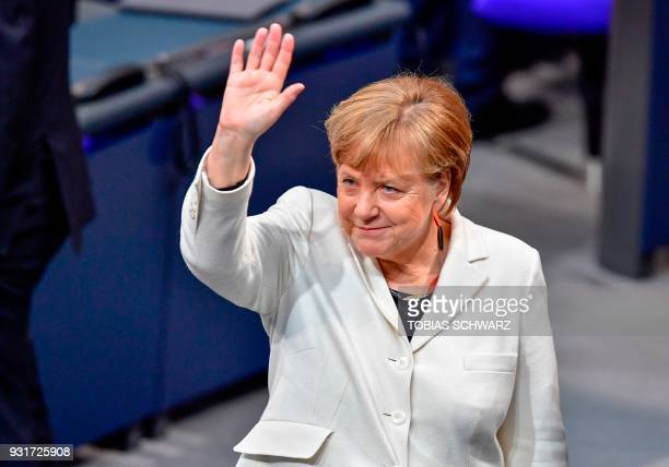 TOPSHOT German Chancellor Angela Merkel waves as she arrives to attends the session for the election of the German Chancellor at the Bundestag on...