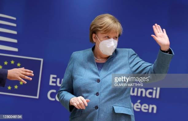 German Chancellor Angela Merkel waves as she attends a round table meeting during an EU summit at the European Council building in Brussels, on...