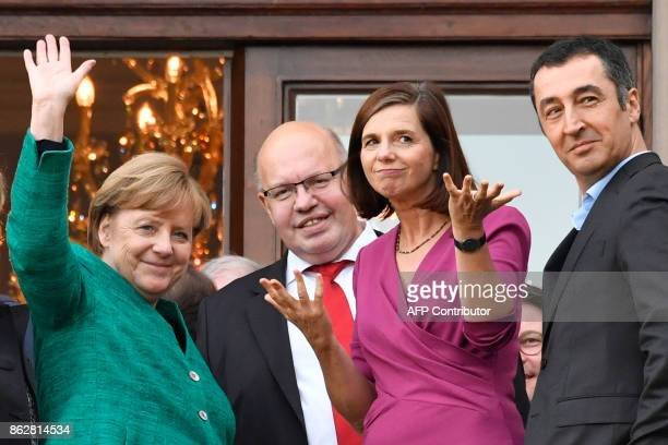 German Chancellor Angela Merkel waves from the balcony as she greets members of the leadership of the Green party including Katrin GoeringEckardt and...