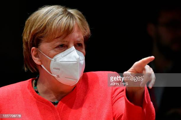 German Chancellor Angela Merkel, wearing a protective face mask, gestures during an EU summit in Brussels on July 20 as the leaders of the European...