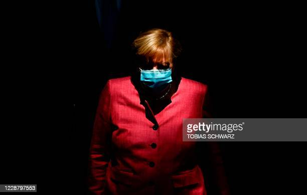German Chancellor Angela Merkel wears a face mask as she arrives for a session of the German lower house of parliament Bundestag in Berlin on...