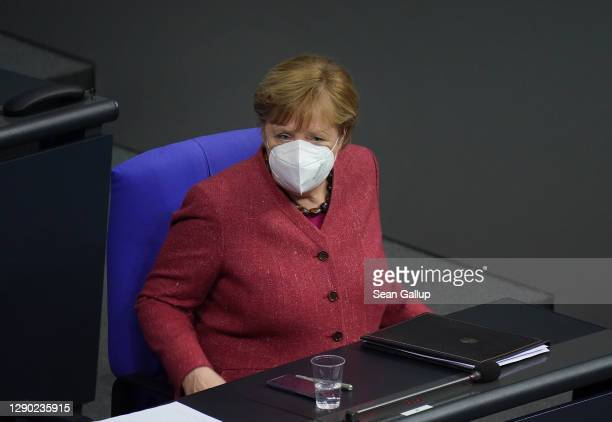 German Chancellor Angela Merkel wears a protective face mask after she spoke during debates over next year's federal budget at the Bundestag during...
