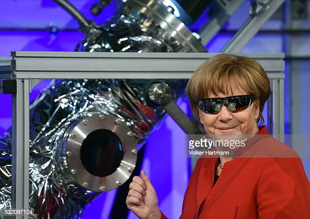 German Chancellor Angela Merkel wears safety goggles while watching an experiment in the DLR_School_Lab Koln during a visit of the European...