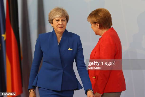 German Chancellor Angela Merkel welcomes British Prime Minister Theresa May at the start of the the G20 summit on July 7 2017 in Hamburg Germany...