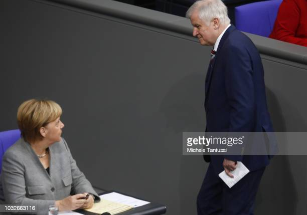 German Chancellor Angela Merkel welcomes Interior Minister Horst Seehofer during a session of the German Parliament or Bundestag on September 13 2018...