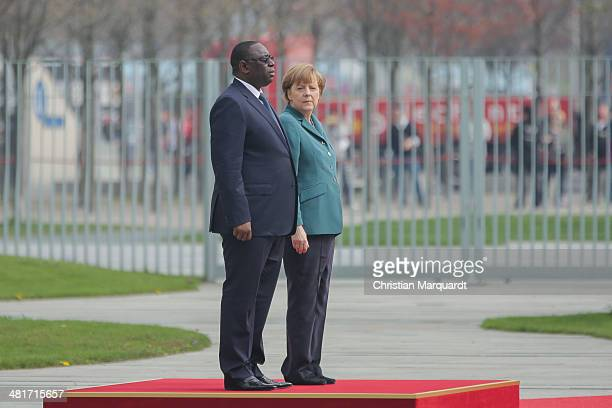 German Chancellor Angela Merkel welcomes President of Senegal Macky Sall with military honors in the Chancellery on March 31 2014 in Berlin Germany...