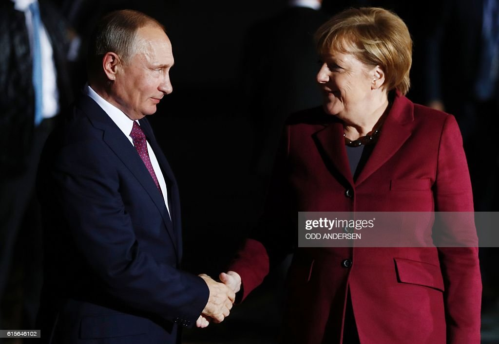 German Chancellor Angela Merkel (R) welcomes Russian President Vladimir Putin at the chancellery on October 19, 2016 in Berlin. German Chancellor Angela Merkel hosts the leaders of Russia, Ukraine and France in a new push for peace in eastern Ukraine. / AFP / Odd ANDERSEN