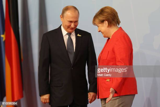 German Chancellor Angela Merkel welcomes Russian President Vladimir Putin at the start of the the G20 summit on July 7 2017 in Hamburg Germany...