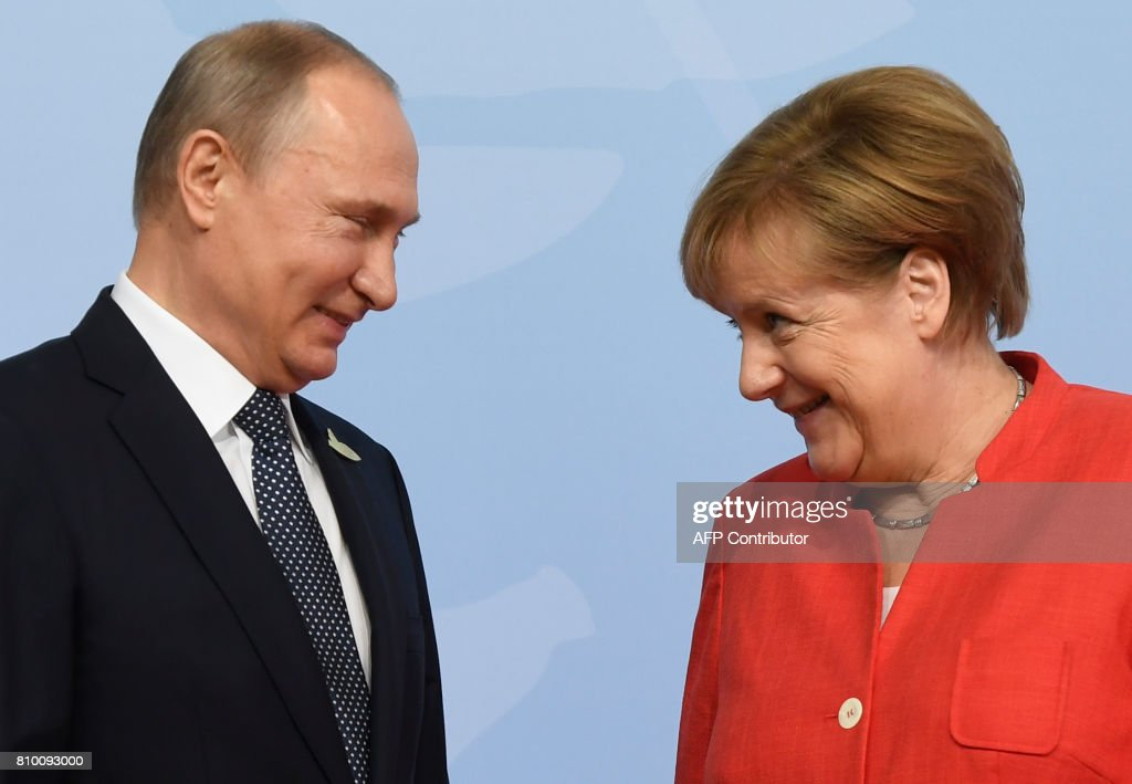 TOPSHOT - German Chancellor Angela Merkel (R) welcomes Russia's President Vladimir Putin as he arrives to attend the G20 summit in Hamburg, northern Germany, on July 7, 2017. Leaders of the world's top economies gather from July 7 to 8, 2017 in Germany for likely the stormiest G20 summit in years, with disagreements ranging from wars to climate change and global trade. /