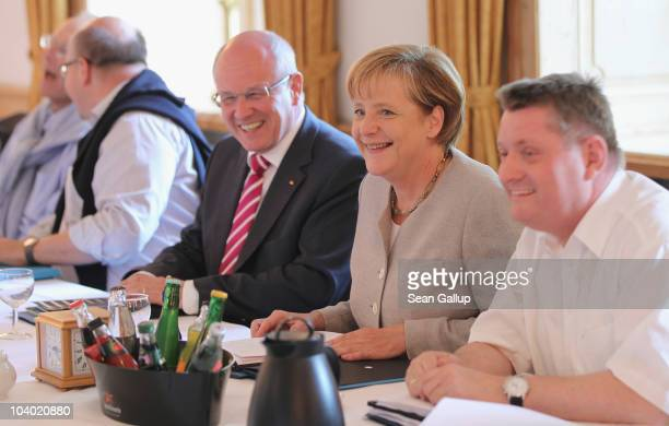 German Chancellor Angela Merkel who is also Chairwoman of the German Christian Democrats sits down next to CDU Bundestag faction leader Volker Kauder...