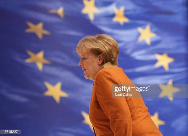 German Chancellor Angela Merkel who is also chairwoman of the German Christian Democratic Union walks past a flag of the European Union as she tours...