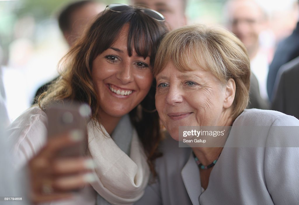 German Chancellor Angela Merkel, who is also chairwoman of the German Christian Democrats (CDU), poses for a selfie during a Mecklenburg-Western Pomerania election campaign event at the Zinzow farming cooperative (Agrargenossenschaft Zinzow) on August 18, 2016 in Boldekow, Germany. Mecklenburg-Western Pomerania, one of Germany's 16 federal states (Bundeslaender), is scheduled to hold elections on September 4. So far the CDU is close in the polls against the German Social Democrats (SPD). The populist Alternative fuer Deutschland (AfD), a political newcomer that is attracting right-wing voters, has double-digit support and will certainly gain seats.
