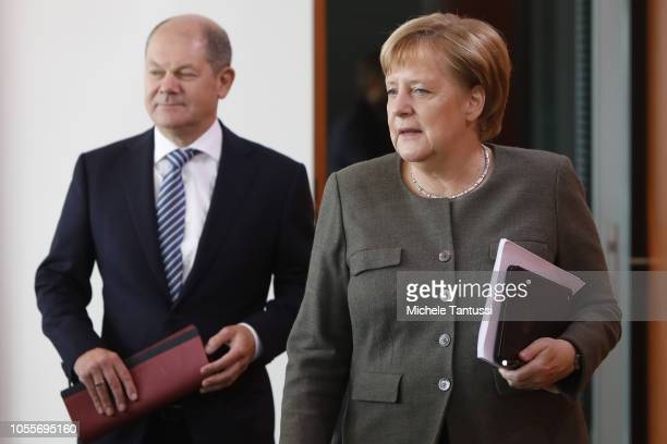 German Chancellor Angela Merkel with Finance Minister and vice Chancellor Olaf Scholz arrive for the weekly government cabinet meeting on October 31...