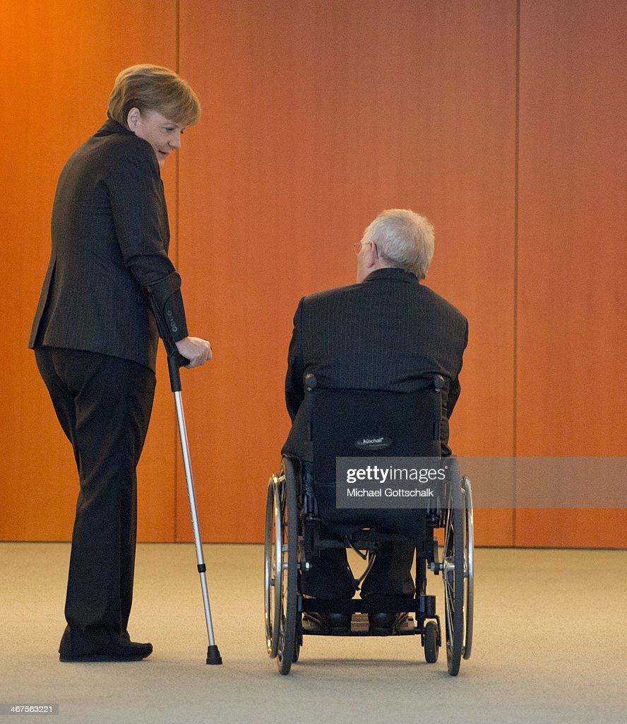 German Chancellor Angela Merkel with her crutches and German Finance Minister Wolfgang Schaeuble in his wheelchair talk to each other on the edge of the presentation of a commemorative coin with a motif of Lower Saxony on the back in the chancellery on February 07, 2014 in Berlin, Germany. The coin is part of a series with motifs from all German federal states.
