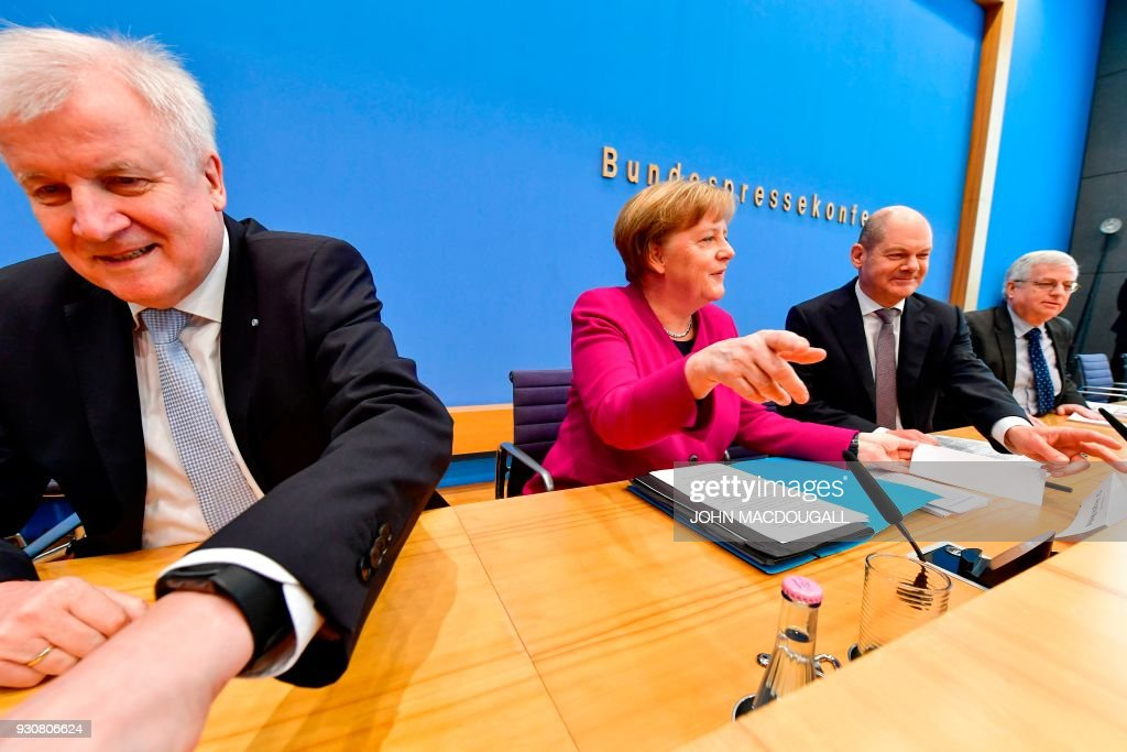 German Chancellor Angela Merkel, with Social Democrats party (SPD) leader and designated German Finance Minister and Vice-Chancellor Olaf Scholz (R) and Bavarian Christian Social Union (CSU) leader and designated Interior minister Horst Seehofer (L) get ready to address a press conference at the Federal Press Conference in Berlin, on March 12, 2018 prior to the signature of the chancellor's conservative CDU/CSU and the SPD's coalition contract for a new government. / AFP PHOTO / John MACDOUGALL