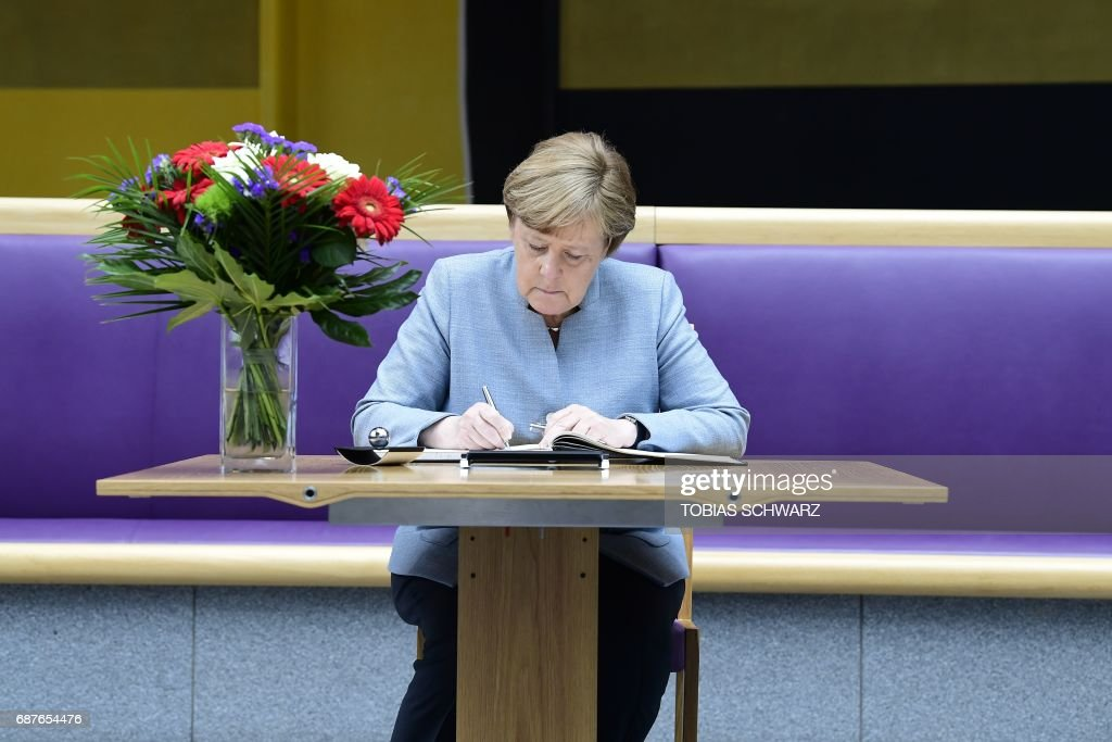 German Chancellor Angela Merkel writes a message in a book of condolence at the British embassy in Berlin, on May 24, 2017, following the terror attack at the Ariana Grande concert at the Manchester Arena in Manchester on May 22. Twenty two people have been killed and dozens injured in Britain's deadliest terror attack in over a decade after a suspected suicide bomber targeted fans leaving a concert of US singer Ariana Grande in Manchester. / AFP PHOTO / POOL / Tobias SCHWARZ