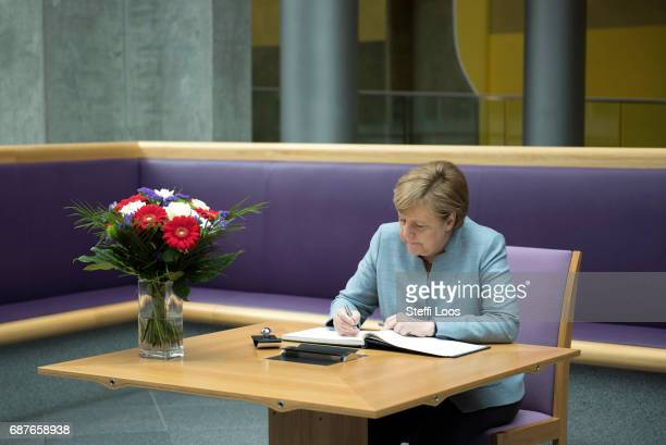 German Chancellor Angela Merkel writes in a book of condolence at the British embassy on May 24 2017 in Berlin Germany An explosion occurred at...