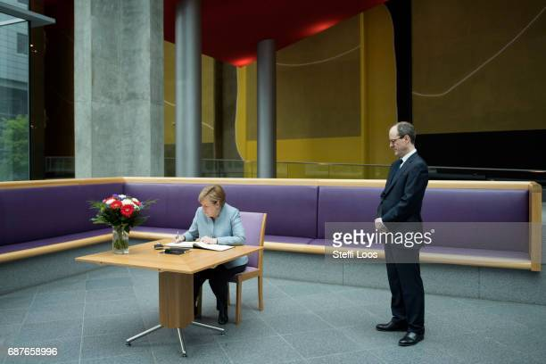 German Chancellor Angela Merkel writes in a book of condolence next to Britains Ambassador to Germany Sir Sebastian Wood at the British embassy on...