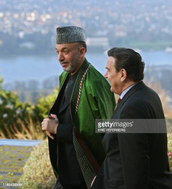 German Chancellor Gerhard Schroeder and Afghan President Hamid Karzai walk together near Petersberg Guesthouse in Bonn on the way to make a group...
