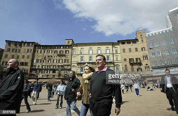 German Chancellor Gerhard Schroeder and his wife Doris walk through Siena's Piazza del Campo 07 April 2004 Schroeder is spending his holiday in...