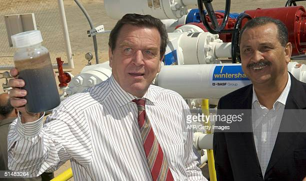 German Chancellor Gerhard Schroeder and Libyan Prime Minister Shukri Mohammed Ghanem look 15 October 2004 at a sample of oil after they opened an oil...