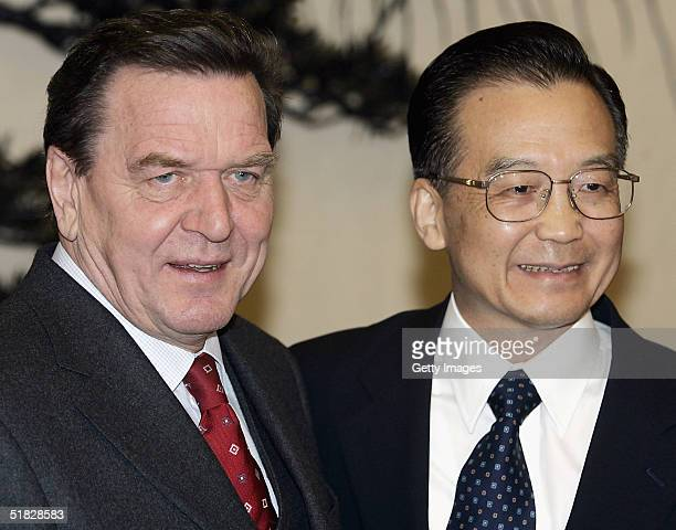 German Chancellor Gerhard Schroeder poses with Chinese Premier Wen Jiabao prior to a meeting at the Great Hall of the People in Beijing on December 6...