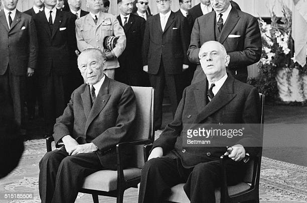 German Chancellor Konrad Adenauer and French President Charles De Gaulle sit side-by-side in Cologne's town hall listening to the welcoming address...
