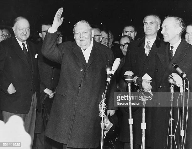German Chancellor Ludwig Erhard waving to the crowd with R A Butler and Sir Alec DouglasHome and other British politicians at Victoria Station London...