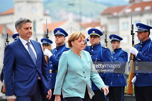 German Chancelor Angela Merkel and Bosnian Prime Minister Denis Zvizdic inspect a Bosnian colour guard upon arrival in Sarajevo on July 9 2015 Merkel...