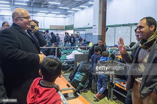 German Chief of Staff Peter Altmaier speaks with refugees in Passau southern Germany as he toured the region on November 4 2015 AFP PHOTO / DPA /...