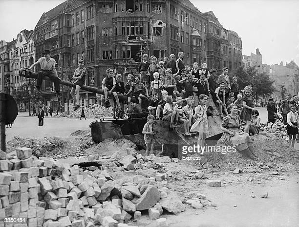 German children playing on a tank in a bombdamaged part of Berlin