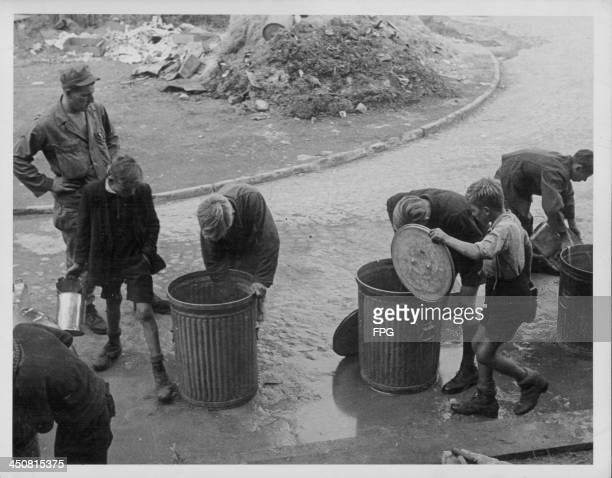 German children salvaging food from trash cans in the street following the end of World War Two a time of great poverty in Germany 1946