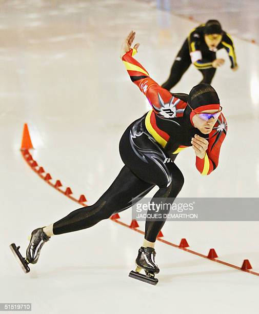 German Christian Breuer and Japanese Takaharu Nakajima skate in the men's 1500m speed skating race at the Utah Olympic Oval 19 February 2002 during...