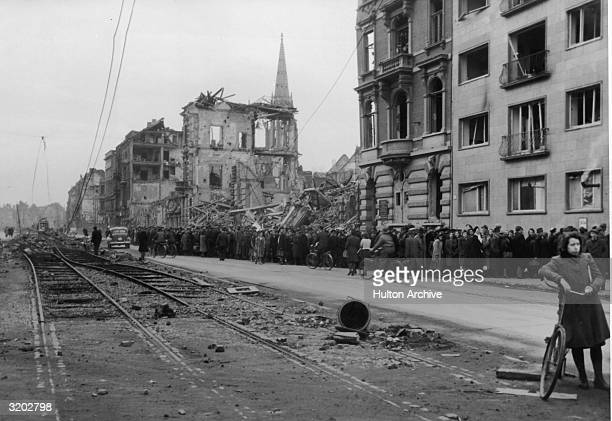 German civilians form a long line in front of bombed out buildings and deserted homes as they wait for food rations Koblenz Germany The mangled...