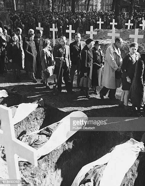 German civilians of Ludwigsluts, Germany, file past the graves of the 200 victims of starvation and torture in the Nazi concentration camp near...
