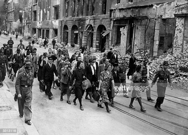 German civilians some of Berlin's black marketeers are seen surrounded by a cordon of German police as they are marched to Police Headquarters in...