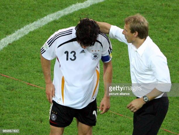 German coach Juergen Klinsmann talks to Michael Ballack after Germany looses 02 after extra time against Italy during the semi final of the 2006 FIFA...