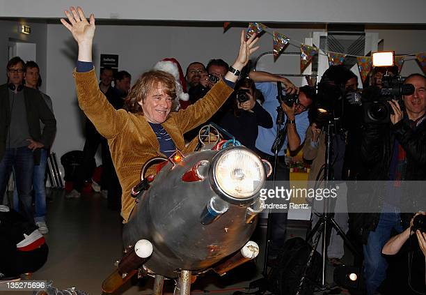 German comedian Helge Schneider poses on a toy rocket during a press conference at Admiralspalast on December 8 2011 in Berlin Germany Schneider...