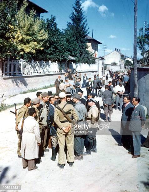 German commanders negotiate a surrender with several clergymen and assorted partisans on a residential street near Milan Italy May 1945