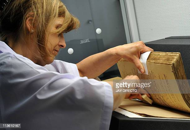 German conservator Monika ScheneiderGast restores the centuryold book titled El Filibusterismo at the National Library in Manila on May 4 2011 The...