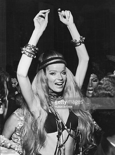 German countess and fashion model Veruschka raises her arms above her head as she dances at a party during Carnaval Rio de Janeiro Brazil February 14...
